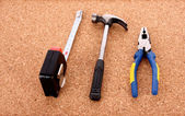 Hammer, zangen und ruller auf kork-board-oberfläche — Stockfoto