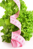 Green fresh lettuce with pink measuring tape — Стоковое фото