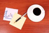 Tasse kaffee, ein paar aufkleber, diagramm und stift auf tabelle zurück — Stockfoto
