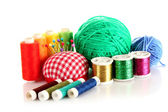 Coloured bobbins of threads, woolen balls and cushion for pins — Stock Photo