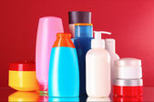 Bottles of health and beauty products on red background — Stock Photo