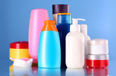 Bottles of health and beauty products on blue background — Stock Photo