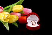 Golden rings and tulips on black background — Stock Photo