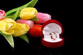Goldene ringe und tulpen auf schwarzem hintergrund — Stockfoto