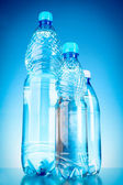 Bottles of water on blue background — Stock Photo