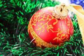 Red Christmas balls among green new year tree — Stock Photo
