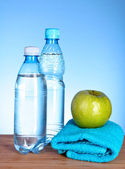 Blue bottle of water, apple, sports towel and measure tape on bl — Stock Photo