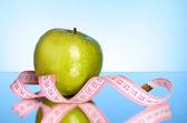 świeże czerwone jabłka smaczne z miara zwijana na niebieskim tle — Zdjęcie stockowe