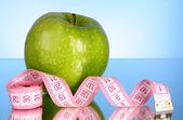 新鲜绿色美味的苹果与测量在蓝色背景上的磁带 — 图库照片