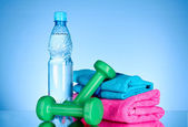 Blue bottle of water, sports towel, measure tape and dumbbells o — Stock Photo