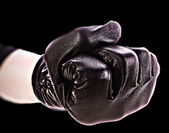 Fist in gloves on black background — Stock fotografie