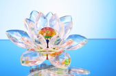 Glass lotus flower on blue background — Stock Photo