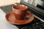 Cup on laptop keyboard — Stock Photo