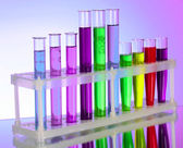 Multicoloured test tubes in the stand on purple background — Stock Photo