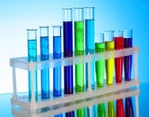 Multicoloured test tubes in the stand on blue background — Stock Photo
