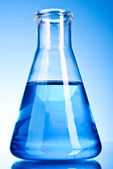 Beaker with blue liquid on blue background — Stock fotografie