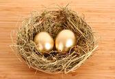 Ovos de galinha dourada três no ninho gramado na mesa de madeira — Fotografia Stock