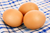 Three brown hen's eggs on the blue chequered cloth — Stock Photo