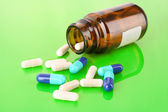 Pill bottle with white and blue pills on green — Stock Photo