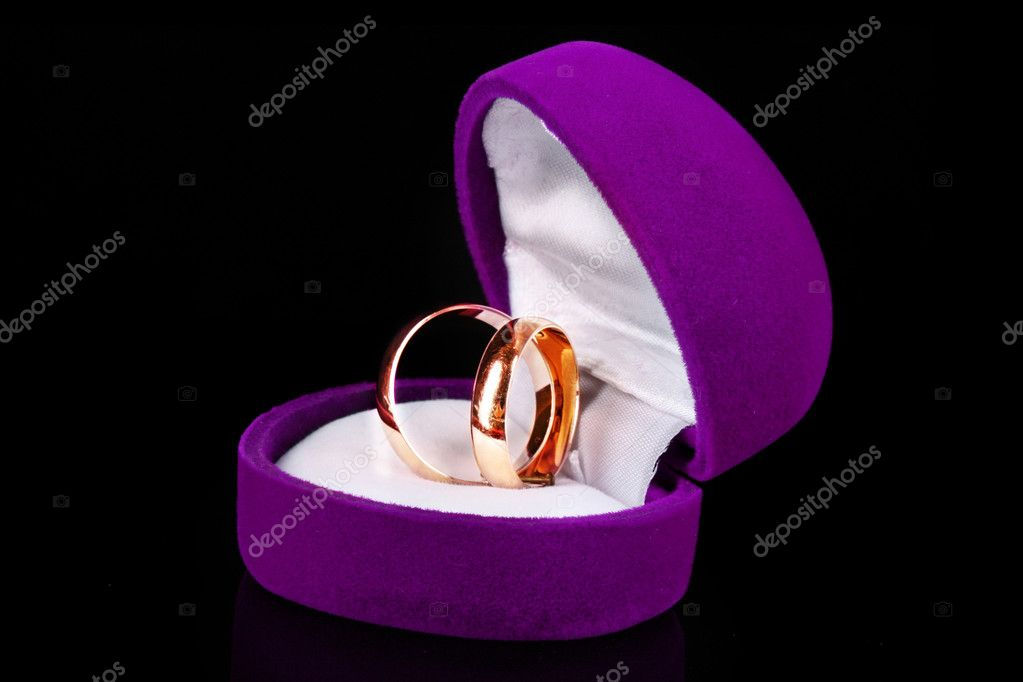 golden wedding rings in purple box isolated on black