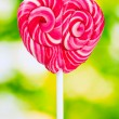 Delicious candy on stick on green background — Stock Photo #6790484