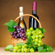 Stock Photo: Bottles of wine and grapes in basket on yellow background