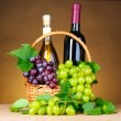 Bottles of wine and grapes in basket on yellow background — Stock Photo