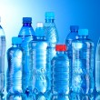 Group plastic bottles of water on blue background — Stock Photo #6790584