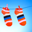 Bright striped socks on line on blue background — Stock Photo