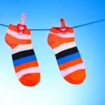 Bright striped socks on line on blue background — Stock Photo #6790600
