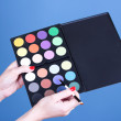 Eye shadows in hand on blue background — Stock Photo