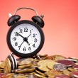 Alarm clock and coins on red background — Stock Photo #6791960