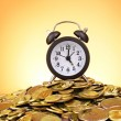 Alarm clock and coins on yellow background — Stock Photo #6792011