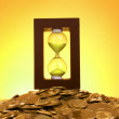 Hourglass and coins on yellow background — Stock Photo