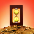 Hourglass and coins on red background - Stock Photo