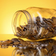 Coins spilling from a money jar on yellow background - Stock Photo