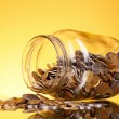 Coins spilling from money jar on yellow background. Ukrainian — Stock Photo #6792108