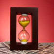 Hourglass and coins on red background — Stock Photo #6792208