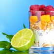 Tasty cornflakes, fruit, milk in glass and mint - Stock Photo