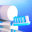 Stock Photo: Toothpaste and toothbrush on blue background