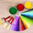 Open cans with bright colors, brushes and palette on wooden table — Stock Photo #6793431