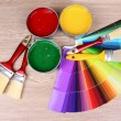 Open cans with bright colors, brushes and palette on wooden table — Stock Photo #6793437