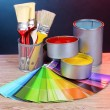 Open cans with bright colors, brushes and palette on wooden table — Stock Photo #6793450