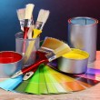 Open cans with bright colors, brushes and palette on wooden table — Stock Photo #6793451