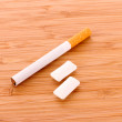 Cigarette and chewing gum on wooden table — Stock Photo