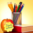 Stationery and apple on yellow background — Stockfoto