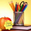 "Stationery and apple with ""I love school"" on yellow background - Stock Photo"