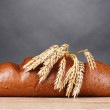 Rye bread and spikelets on wooden table on gray background — Stock Photo