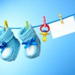 Baby booties, nipple and white card on a blue background — Stock Photo #6794581