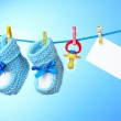 Baby booties, nipple and white card on a blue background — Stock Photo